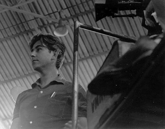 Ary Fernandes ao lado de um avião no hangar, diringindo uma cena do Águias.